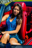 Beautiful girl sitting in to a vintage Ford Mustang GT. Stock Images