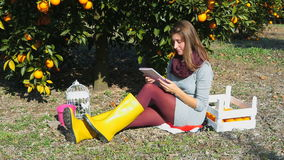 Beautiful girl sitting under the orange tree. Reading a book and daydreaming on sunny autumn day stock footage