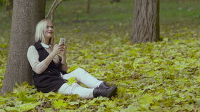 Beautiful girl sitting under a tree in the autumn park smiling and reading messages with a cell phone in her hands.  stock footage