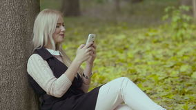 Beautiful girl sitting under a tree in the autumn park smiling and reading messages with a cell phone in her hands stock footage