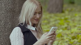 Beautiful girl sitting under a tree in the autumn park smiling and reading messages with a cell phone in her hands stock video