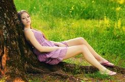 Beautiful girl sitting under the tree Stock Image