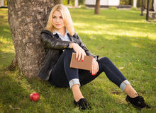 Beautiful girl sitting under a tree and holding a book Royalty Free Stock Photo
