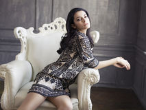 Beautiful girl sitting in a vintage armchair Royalty Free Stock Photos