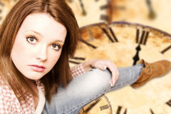 Beautiful girl sitting on vintage clocks Royalty Free Stock Images