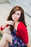 Beautiful girl sitting at a wall Stock Image