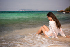 Beautiful girl sitting in a waves on the beach Stock Photos
