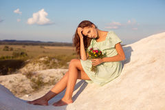 Beautiful girl sitting on white hills on the sunset. Pretty suntanned girl with bouquet of flowers sitting on mountains with amazi Stock Photo