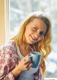 beautiful girl sitting by the window with cup of tea or c Stock Photo