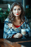 Beautiful girl sitting wrapped in a blanket, next to coffee. Stock Images