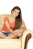 Beautiful girl sitting on a yellow skin sofa Stock Photo
