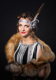 The beautiful girl with a skin of  fox on shoulders and  feather in  hairstyle in Chicago style Stock Photography