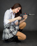 Beautiful girl in a skirt with a drill Royalty Free Stock Photo