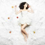 Beautiful Girl Sleeping. Caucasian girl sleeping on white fabric after eating an apple. Fairy-tale theme Royalty Free Stock Photo
