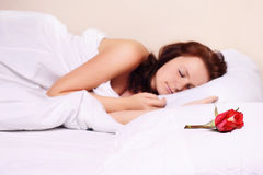 Beautiful girl sleeping in bed. With rose Stock Photo