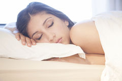 Beautiful girl sleeping in bed. A beautiful girl sleeping in her bed, hugging her pillow Royalty Free Stock Images