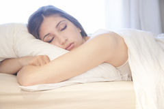 Beautiful girl sleeping in bed. A beautiful girl sleeping in her bed, hugging her pillow Royalty Free Stock Image