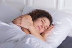 Beautiful girl sleeping in bed alone. Beautiful girl sleeping alone in bed on the left side Stock Photo