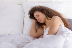 Beautiful girl sleeping in bed alone. Beautiful girl sleeping alone in bed on the right side Royalty Free Stock Image