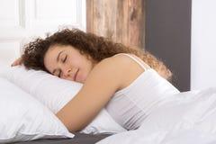 Beautiful girl sleeping in bed alone. Beautiful girl sleeping alone in bed on the right side Stock Image