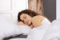 Beautiful girl sleeping in bed alone. Beautiful girl sleeping alone in bed on the right side Royalty Free Stock Images