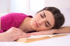 Beautiful girl sleeping on bed with book. Stock Photography