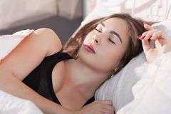 Beautiful girl sleeping in bed early in morning. Portrait of young beautiful woman having rest in her bed. Drunk dream, sleeping pill, exhaustion, tiredness Stock Photos