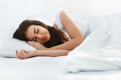 Beautiful girl sleeping in the bedroom. Happy beautiful caucasian girl sleeping on the pillow iin comfortable bed in the bedroom at home in the morning. White Royalty Free Stock Image