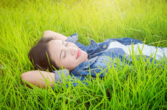 Beautiful girl sleeping on grass field Stock Photos