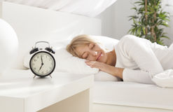 Beautiful girl sleeping in her bed.  focus on clock. Beautiful girl sleeping in her bed. clock on the nightstand. focus on clock Royalty Free Stock Photography