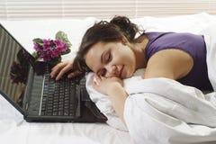 Beautiful girl sleeping with laptop. Beautiful girl sleeping in bed with laptop Stock Photography