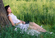 Beautiful girl sleeping in nature after reading book. On sunny summer day Stock Photography
