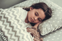 Beautiful girl sleeping. Beautiful school girl is sleeping with a teddy bear in her bed at home Royalty Free Stock Photos