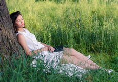 Beautiful girl sleeping in summer nature after reading book. Beautiful girl sleeping in nature after reading book on sunny summer day Stock Photo