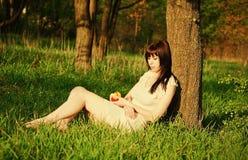 Beautiful girl sleeping under the tree. Beautiful young girl sleeping under the tree with apple in hands. Sunset time Stock Photos