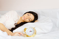 Beautiful girl sleeping in white nightclothes. Picture of beautiful girl sleeping in white lace nightclothes. Young woman holding golden retro alarm clock on Royalty Free Stock Photos