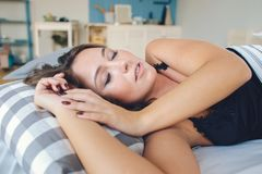 Beautiful young brunette woman sleeping in a white bed. stock images