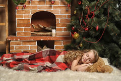Girl sleeps beside a Christmas tree Royalty Free Stock Photo