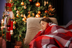 Beautiful girl sleeps. Beautiful girl sleeping near a Christmas tree Stock Photo