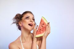 Beautiful girl with a slice of watermelon on light studio background. Fashion food photography