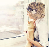 Beautiful girl with small dog looking through window Royalty Free Stock Photos