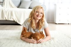 Beautiful girl with small rabbits. At home Royalty Free Stock Images