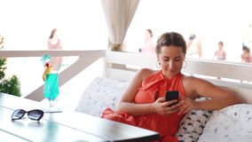Beautiful girl with smartphone chilling in cafe.
