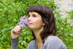 Beautiful girl smell the lilacs royalty free stock photography