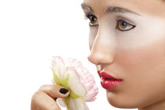 Beautiful girl smelling a flower with a white eyeshadow makeup Royalty Free Stock Photos