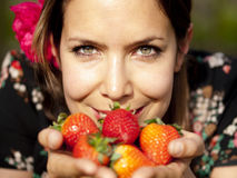 Beautiful girl smelling fresh strawberries in the spring Royalty Free Stock Image