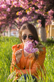 Beautiful girl smelling a pink sakura flowers Royalty Free Stock Photography
