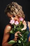 Beautiful girl smelling roses Stock Images