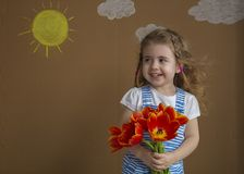 Beautiful girl with smile in the blue dress with flowers tulips in hands on a light background with painted sun and. Beautiful girl in the blue dress with Royalty Free Stock Photos