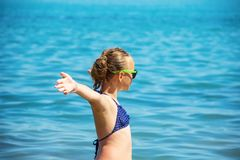Beautiful girl smile with raised hands, woman on beach summer vacation. concept of freedom travel. royalty free stock image